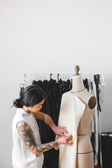 Young Fashion Designer Working with Mannequin in a White Studio