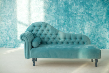 Blue couch on a background of white blue screen on the wall