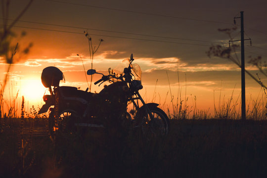 Silhouette of a motorcycle on the road at sunset