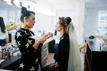 Gorgeous bride having her hair and makeup done in the beauty salon.
