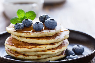 Blueberry buttermilk pancakes with maple syrup on rustic table