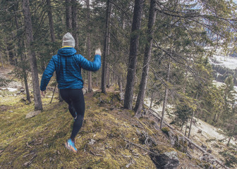Runner jumping and running down forest mountains trail in spring