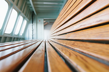 Low-angle closeup of wooden benches on a ferry boat