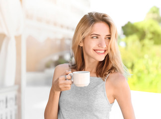 Young woman drinking coffee while standing on balcony