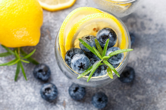 Refreshing summer drink with lemon, blueberries, rosemary and ice cubes. Detox, lemonade, cocktail. Selective focus