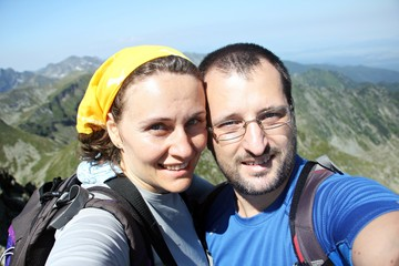Portrait of a happy couple taking selfie in the high mountains.