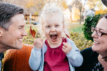 Laughing child between her Mom and Dad