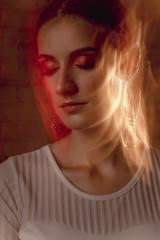 Closeup portrait of pretty model in mixed light at studio