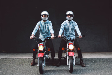 Two young men sitting on motorcycles in alleyway