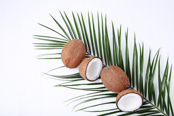 Coconuts with green leaf on white wooden table