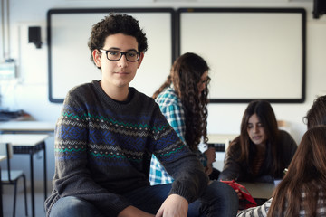 Aware portrait of young man student with group of teenagers