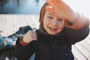 Cute young boy laughing and looking at camera