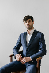Elegant Young Man in Blue Tuxedo Sitting on Old Chair