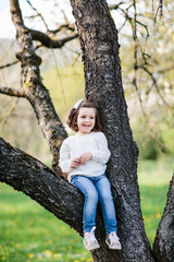 Small girl sitting on a branch of the tree