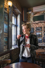 Young woman smiling and drinking coffee in a pub