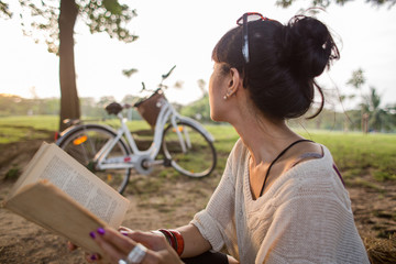 Asian woman reading a book in a park