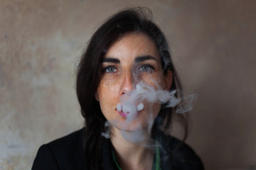 Portrait of a young woman blowing a cigarette smoke