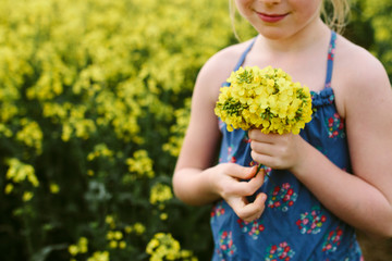 A little girl holding a posy of yellow rape flowers