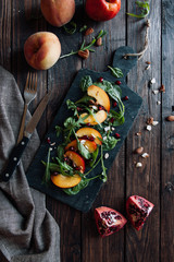 Fresh peach salad with arugula, spinach, almonds and pomegranate