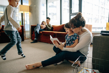 Young mom teaching little girl to read inside