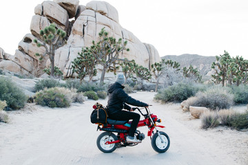 young male riding motor bike in desert