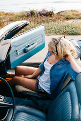 woman looking away from camera sitting in convertible car next to beach