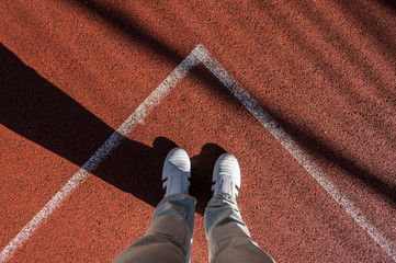 White sneakers in corner of sport field, footsie, personal perspective