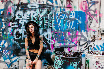 A woman sitting down in a graffiti alley way in the city