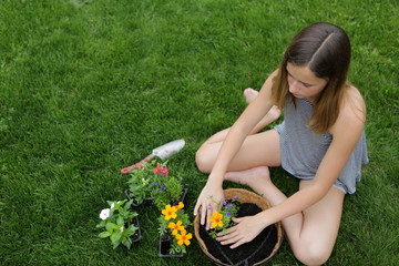 A Teenage Girl Planting A Colorful Basket Of Flowers