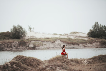 Young woman in a red dress sitting on a hill