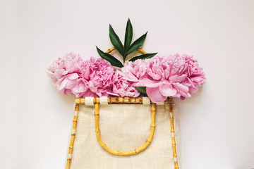 summer bag filled with pink peonies