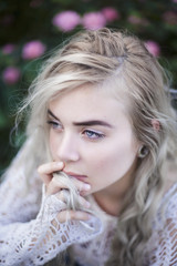 Young beautiful woman with grey hair and blue eyes in roses