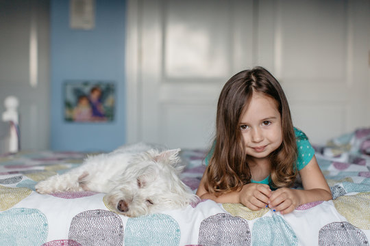 Beautiful young girl laying on her bed with a dog