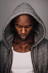 Young African man in hoodie looking down
