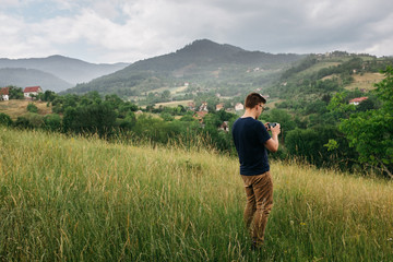 young male on valley hillside taking picture of the photographic landscape