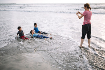 A mother takes pictures of her sons at the beach