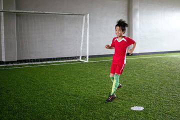 Young kid having fun playing indoor football on turf