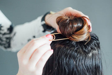 Woman putting a hairpin in friend's hair