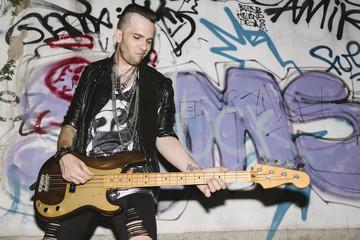 Punk rocker playing bass guitar at the club