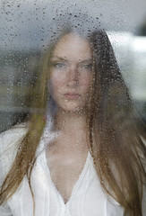 portrait of young woman behind window with raindrops