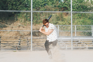 Portrait of young man holding bat on baseball field
