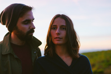 Portrait of a couple standing on the mountain at sunset.