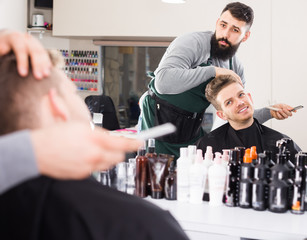Smiling man hairdresser making haircut to client