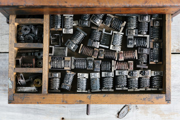 Old wood drawer filled with vintage metal numbering inserts for printer - from above