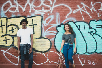 Couple standing in front of graffiti wall