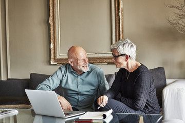 Senior Business Couple Discussing Over Laptop
