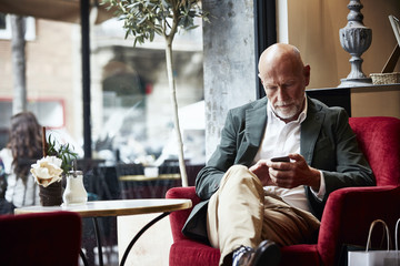 Senior Man Using Mobile Phone In Restaurant
