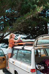 Young Woman Tying Surfboards to the Roof of a Retro Wagon