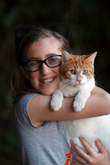 Young Girl Wearing Glasses Holding Orange and White Cat