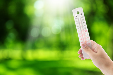 Tropical temperature holding hand on nature background, measured on an outdoor thermometer, environment concept.